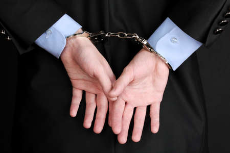 Businessman hands fettered with handcuffs