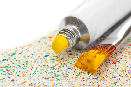 brushes with colorful paint and tube with watercolor on colorful splashes background close-up photo