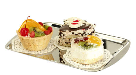sweet cakes with fruits and chocolate on silver tray isolated on white photo