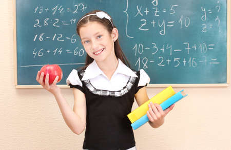 beautiful little girl in school uniform with books and apple in class room photo