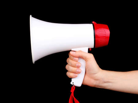 speaking trumpet: red and white megaphone in hand isolated on black