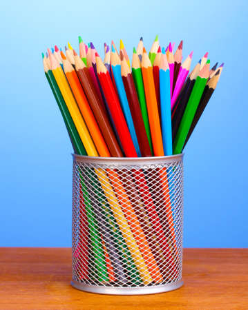 Color pencils in glass on wooden table on blue background photo