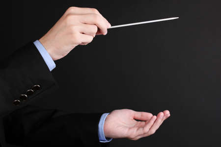 louder: Music conductor hands with baton isolated on black