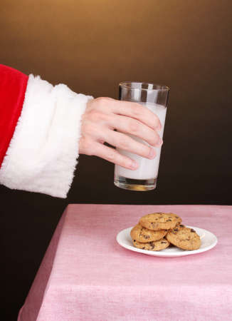 hots: Santa Claus hand holding glass of milk on brown background