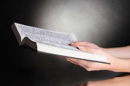 bible ouverte: Les mains des femmes sur ouvert russe sainte bible sur fond noir backround Banque d'images