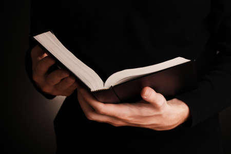 black jesus: Hands holding open russian bible on black background