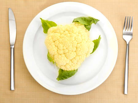 Fresh cauliflower and measuring tape on plate, knife and fork isolated on white photo