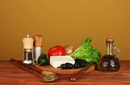 Ingredients for a Greek salad on brown background close-up photo