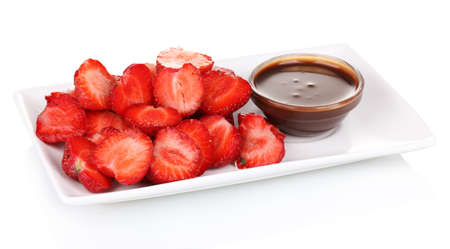 Fresh strawberries on plate with chocolate isolated on white photo