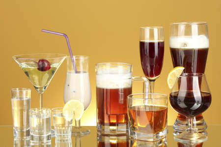 a variety of alcoholic drinks on yellow background photo
