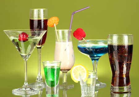 a variety of alcoholic drinks on green background photo