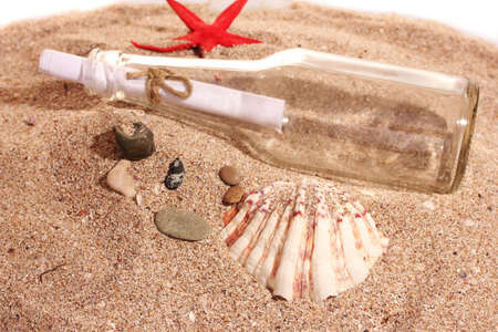 Glass bottle with note on sand shore with seashells photo