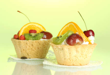 sweet cakes with fruits on green background photo