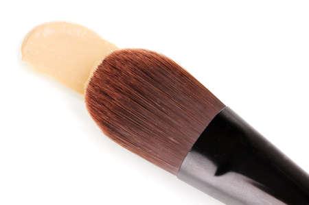 Cosmetic liquid foundation and brush isolated on white photo