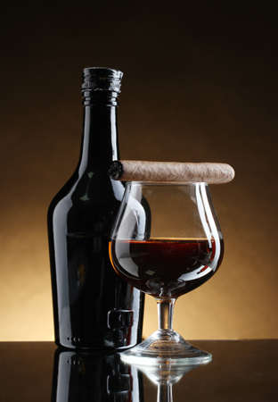 bottle and glass of brandy and cigar on brown background photo
