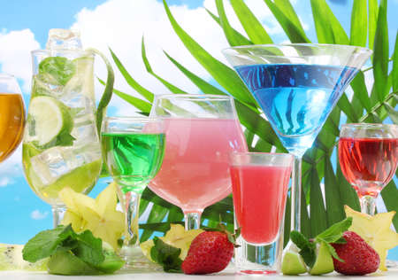 Glasses of cocktails on table on blue sky background Stock Photo - 14322228