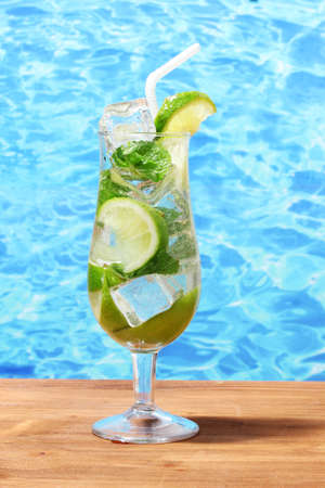 cold fresh lemonade on wooden table on sea background photo