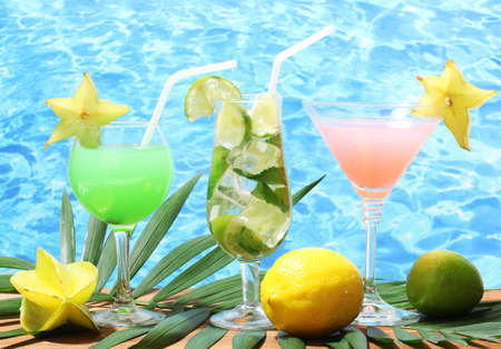 Glasses of cocktails on wooden table on blue sea background photo