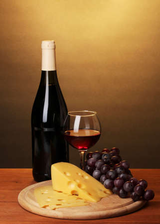 Bottle of great wine with wineglass and cheese on wooden table on brown background photo