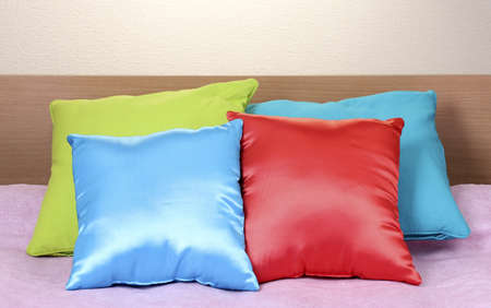 bright pillows on bed on beige background photo