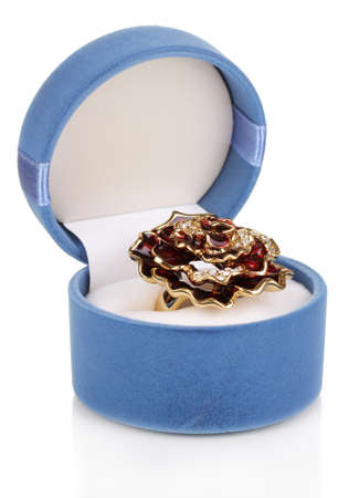 Gold ring with big red flower and clear crystals in blue velvet box isolated on white photo
