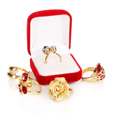 Gold ring with blue, black, lilac and clear crystals in red velvet box and four golden rings isolated on white photo