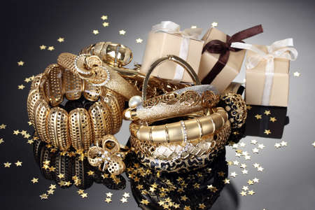 Beautiful golden jewelry and gifts on grey background 스톡 콘텐츠