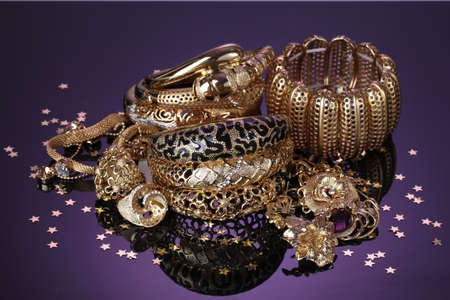 Beautiful golden jewelry on purple background photo