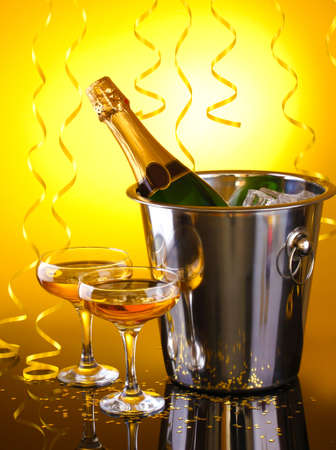 celebration champagne: Champagne bottle in bucket with ice and glasses of champagne, on yellow background