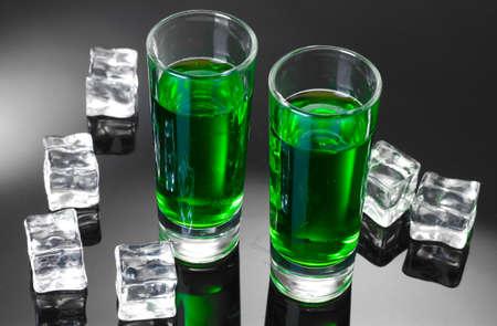 ajenjo: Dos vasos de absenta y el hielo sobre fondo gris Foto de archivo