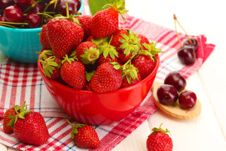 Ripe strawberries and cherry berries in bowls on white wooden table photo