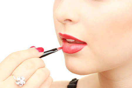 beautiful woman applying lip gloss photo