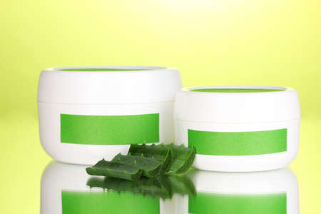 Jars of cream with aloe vera on green background photo