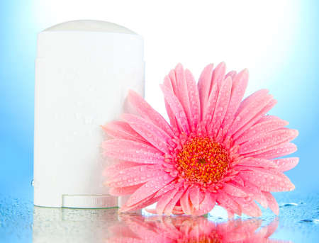 deodorant with flower on blue background photo