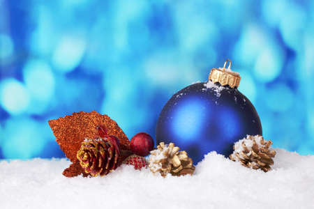 beautiful blue Christmas ball and branch on snow on blue background photo