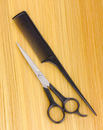 Shiny blond hair with hair cutting shears and comb close-up photo