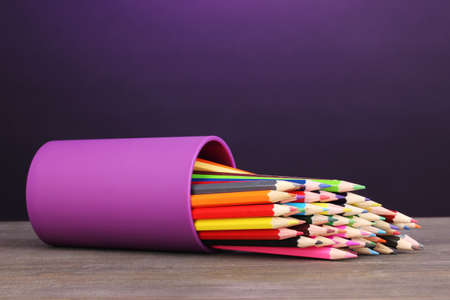 Color pencils in glass on wooden table on violet background Stock Photo - 14343423
