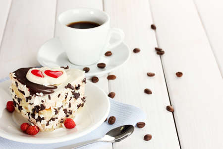 sweet cake with chocolate on plate and cup of coffee on wooden table photo