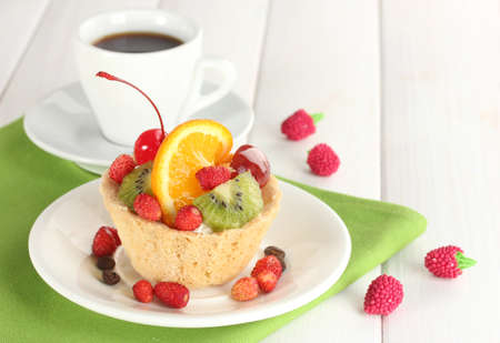 fruit cake: sweet cake with fruits on plate and cup of coffee on wooden table
