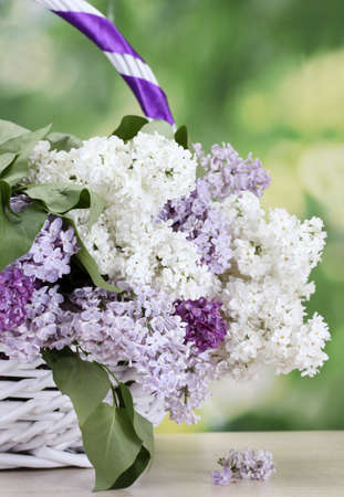 beautiful lilac flowers in basket on wooden table on green background photo