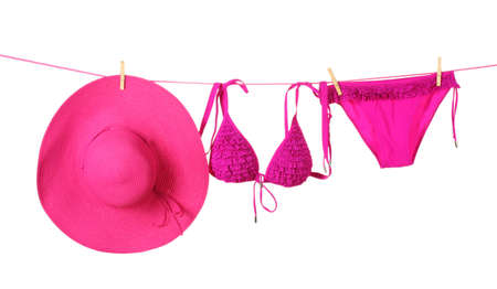 Womens swimsuit and hat hanging on a rope on white background photo