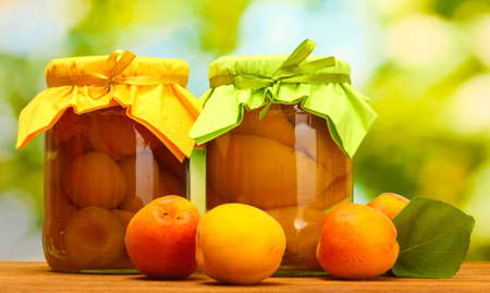 canned apricots in a jars and sweet apricots on wooden table on green background photo