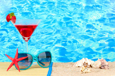 Beach composition of fashionable womens sunglasses and a refreshing drink photo
