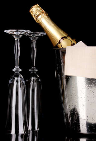 Champagne bottle in bucket with ice and glasses isolated on black photo