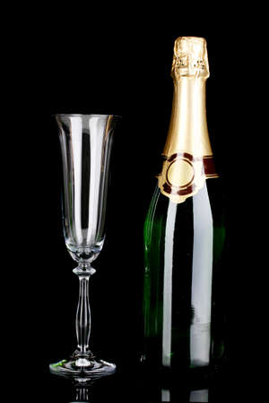 gold capped: Bottle of champagne and goblet isolated on black
