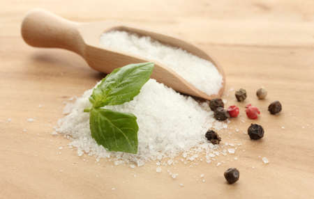 salt with fresh basil, garlic and pepper on wooden table photo