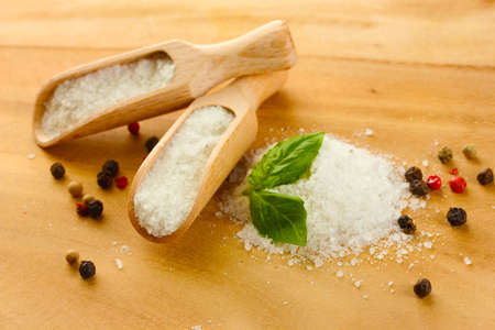 salt with fresh basil and and pepper on wooden table photo
