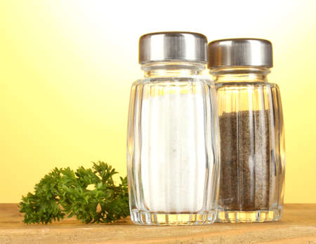 Salt and pepper mills and parsley on wooden table on yellow background photo