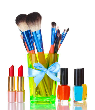 make-up brushes in cup and cosmetics isolated on white photo