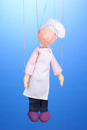 Wooden puppet as cook on blue background photo